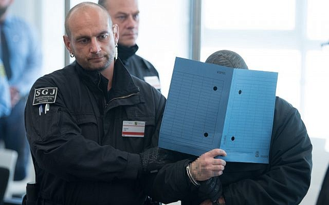 """One of the defendants of the so-called """"Revolution Chemnitz"""" is brought to the courtroom in Dresden, eastern Germany, on September 30, 2019, on the first day of the trial of an alleged neo-Nazi terrorist cell accused of plotting violent political upheaval in Germany. (Sebastian Kahnert/Pool/AFP)"""
