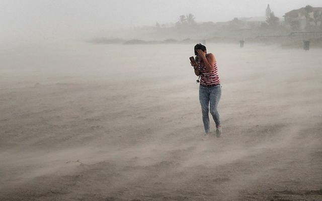 A woman seeks cover from wind, blowing sand and rain whipped up by Hurricane Dorian as she walks on the beach on September 2, 2019 in Cocoa Beach, Florida. (Scott Olson/Getty Images/AFP)