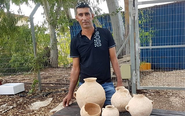 Ahmed Nassar Yassin with 4,500-year-old artifacts he discovered in a burial cave near Araba in northern Israel. (Nir Distelfeld/Israel Antiquities Authority)