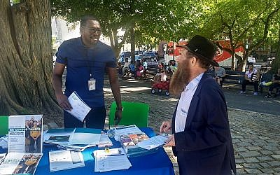 Rabbi Eli Cohen (right), the executive director of the Crown Heights Community Center, talks with a census volunteer at the #OneCrownHeights festival in Brooklyn, New York on Sunday, September 15, 2019. (Ben Sales/via JTA)