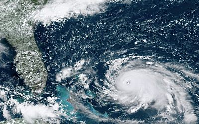 This GOES-16 satellite image taken on August 31, 2019, at 16:00 UTC and provided by National Oceanic and Atmospheric Administration (NOAA), shows Hurricane Dorian, right, churning over the Atlantic Ocean. (NOAA via AP)