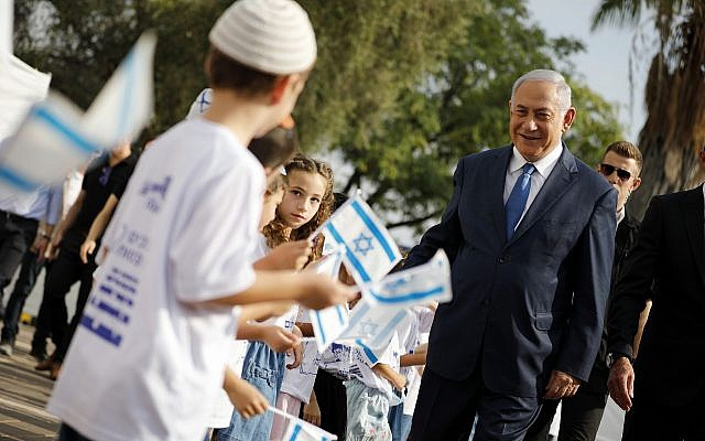 Prime Minister Benjamin Netanyahu, right, greets students as they wave Israeli flags during a ceremony opening the school year in the settlement of Elkana in the West Bank Sunday, Sep. 1, 2019. (Amir Cohen/Pool Photo via AP)
