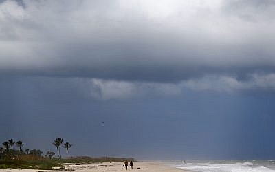 People walk on a largely deserted beach of the Atlantic Ocean on the barrier island in Vero Beach, Fla., Sunday, Sept. 1, 2019. The barrier island is under a voluntary evacuation today and a mandatory evacuation tomorrow in preparation for the possibility of Hurricane Dorian making landfall. (AP Photo/Gerald Herbert)