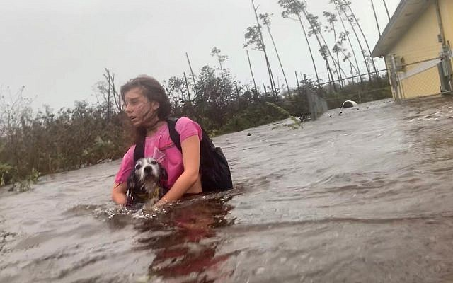 Julia Aylen wades through waist deep water carrying her pet dog as she is rescued from her flooded home during Hurricane Dorian in Freeport, Bahamas, September 3, 2019. (AP Photo/Tim Aylen)