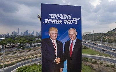 A worker hangs an election campaign billboard of the Likud party shows Prime Minister Benjamin Netanyahu, right, and US President Donald Trump in Tel Aviv, Israel  on September 8, 2019. Hebrew on billboard reads 'Netanyahu, in another league.' (AP/Oded Balilty)