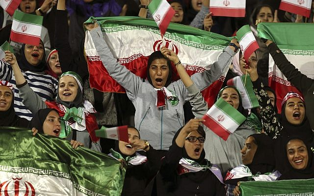 In this photo from October 16, 2018, Iranian women cheer as they wave their country's flag after authorities in a rare move allowed a select group of women into Azadi stadium to watch a friendly soccer match between Iran and Bolivia, in Tehran, Iran. (AP Photo/Vahid Salemi, File)