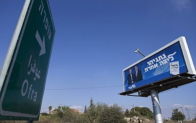 An election campaign billboard for the Likud party shows Prime Minister Benjamin Netanyahu and US  President Donald Trump, facing a road sign directing traffic to the West Bank Israeli settlement of Ofra, north of Ramallah, September 11, 2019 (AP Photo/Nasser Nasser)