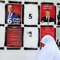In this September 4, 2019 file photo, a woman walks past a wall of campaign posters in Tunis, Tunisia. (AP Photo/Hassene Dridi, File)