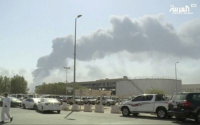 Screen capture from a video broadcast on the Saudi-owned Al-Arabiya satellite news channel showing a man walking through a parking lot as the smoke from a fire at the Abqaiq oil processing facility can be seen behind him in Buqyaq, Saudi Arabia., September 14, 2019. (Al-Arabiya via AP)