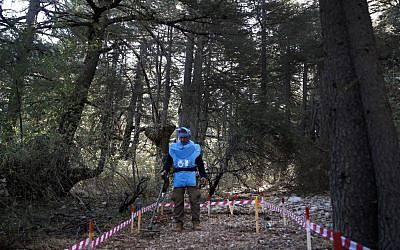 In this Sept. 18, 2019 photo, a Lebanese deminer from Humanity and Inclusion, a French-based international non-governmental organization, uses a mine detector at a cedar forest, in Hadath El-Jebbeh, north Lebanon (AP Photo/Hussein Malla)
