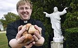In this  Sept. 24, 2019 photo, The Rev. Andrew K. Nelson, pastor of Saint Ignatius of Loyola Parish in Somersworth, New Hampshire and Saint Mary Parish in Rollinsford, New Hampshire holds tulip bulbs which will be planted at the church on High Street in Somersworth (Deb Cram/Foster's Daily Democrat via AP)