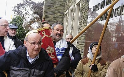 This 2017 photo provided by fellow congregant Barry Werber shows Richard Gottfried carrying a Torah outside the Tree Of Life building in Pittsburgh. Gottfried was among the 11 killed by an anti-Semitic gunman on Oct. 27, 2018. (Barry Werber via AP)