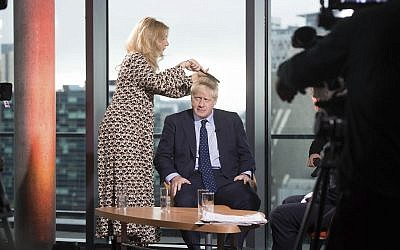 British Prime Minister Boris Johnson has his hair combed as he prepares to appear on a TV political show at Media City in Salford, England, before opening the Conservative party annual conference on September 29, 2019. (Stefan Rousseau/PA via AP)