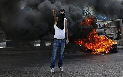 An anti-government protester makes victory sign next to tires that were set on fire to block a road during a demonstration, in Beirut, Lebanon, Sunday, Sept. 29, 2019. (AP Photo/Bilal Hussein)