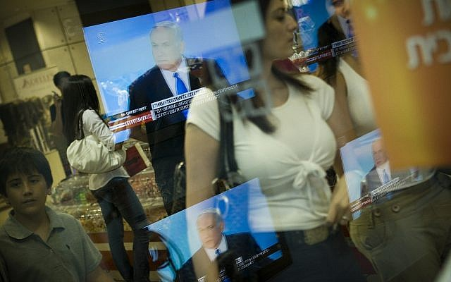 Television images of Israeli Prime Minister Benjamin Netanyahu are reflected on a shop window in Jerusalem, Sunday June 14, 2009.  (AP/Bernat Armangue)