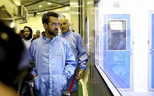 In this Aug. 31, 2019 photo, Iran's Minister of Information and Communications Technology Mohammad Javad Azari Jahromi looks at The Nahid-1 domestically built satellite at the space research center in Tehran, Iran. (Information and Communications Technology via AP)