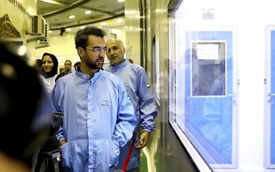 In this August 31, 2019 photo, Iran's Minister of Information and Communications Technology Mohammad Javad Azari Jahromi looks at The Nahid-1 domestically built satellite at the space research center in Tehran, Iran. (Information and Communications Technology via AP)