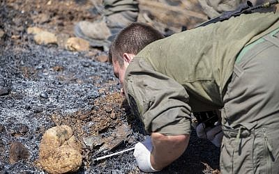 An Israeli soldier examines the remains of a rocket near the village of Avivim on the Israel-Lebanon border, Monday, Sept. 2, 2019. (AP Photo/Ariel Schalit)
