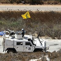 Spanish UN peacekeepers patrolling along the Lebanese-Israeli border pass a Hezbollah flag, in the southern Lebanese village of Kfar Kila, Lebanon, Monday, Sept. 2, 2019. (AP Photo/Hussein Malla)