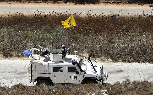 Spanish UN peacekeepers patrolling along the Lebanese-Israeli border pass a Hezbollah flag, in the southern Lebanese village of Kfar Kila, Lebanon, September 2, 2019. (AP Photo/Hussein Malla)