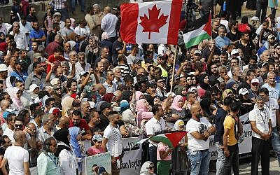 Hundreds of Palestinian refugees waving Palestinian and Canadian flags request asylum at a rally outside the Canadian Embassy, in Beirut, Lebanon, September 5, 2019. (AP Photo/Hussein Malla)