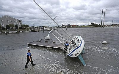Beaufort Police Officer Curtis Resor, left, and Sgt. Micheal Stepehens check a sailboat for occupants in Beaufort, N.C. after Hurricane Dorian passed the North Carolina coast on Friday, Sept. 6, 2019. (AP Photo/Tom Copeland)