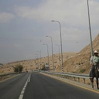 A Palestinian man rides a donkey on a main road in the Jordan Valley, near Tubus, in the West Bank, September 11, 2019. (Ariel Schalit/AP)