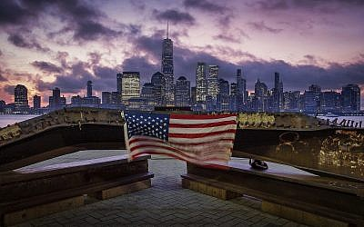 A US flag hanging from a steel girder, damaged in the September 11, 2001, attacks on the World Trade Center, blows in the breeze at a memorial in Jersey City, New Jersey, September 11, 2019, as the sun rises behind One World Trade Center building and the re-developed area where the Twin Towers of World Trade Center once stood in New York City on the 18th anniversary of the attacks. (AP Photo/J. David Ake)