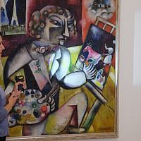 Stedelijk Museum Conservator Meta Chavannes shines a flashlight on a Marc Chagall self portrait, in Amsterdam, Friday, Sept. 13, 2019, during a presentation of results of a five-year research project into the painter. (AP Photo/Mike Corder)