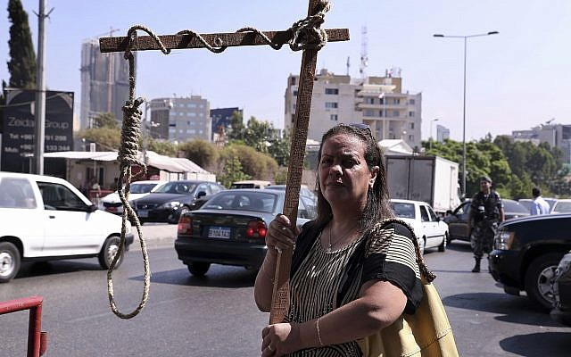 A former inmate of Khiam prison holds a mock gallows during a sit-in near a military court where an arrest warrant was issued for Lebanese-American Amer Fakhoury, who confessed he had worked for Israel when it had a security zone in Lebanon for nearly two decades, in Beirut, Lebanon, September 17, 2019. (Bilal Hussein/AP)