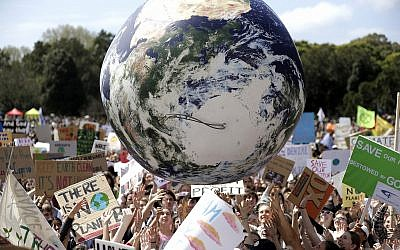 A large inflatable globe is bounced through the crowd as thousands of protestors, many of them school students, gather in Sydney, Sept. 20, 2019, calling for action to guard against climate change (AP Photo/Rick Rycroft)