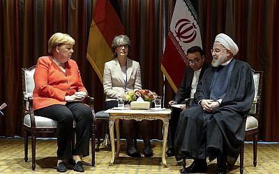 In this photo released by the official website of the office of the Iranian Presidency, President Hassan Rouhani (R) meets Germany's Chancellor Angela Merkel (L) on the sideline of the United Nations General Assembly at the UN Headquarters Sept. 24, 2019. (Iranian Presidency Office via AP)