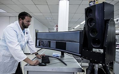 In this Sept. 9, 2019 photo, Ariel Gomez, a systems engineer at Israel Aerospace Industries, works on the Popstar system at Israel Aerospace Industries, in the town of Yehud. (AP Photo/Tsafrir Abayov)