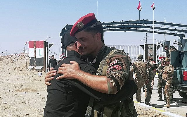 Iraqi and Syrian border guards soldiers congratulate each other during the opening ceremony of the crossing between the Iraqi town of Qaim and Syria's Boukamal in Anbar province, Iraq, September 30, 2019. (AP Photo/Hadi Mizban)
