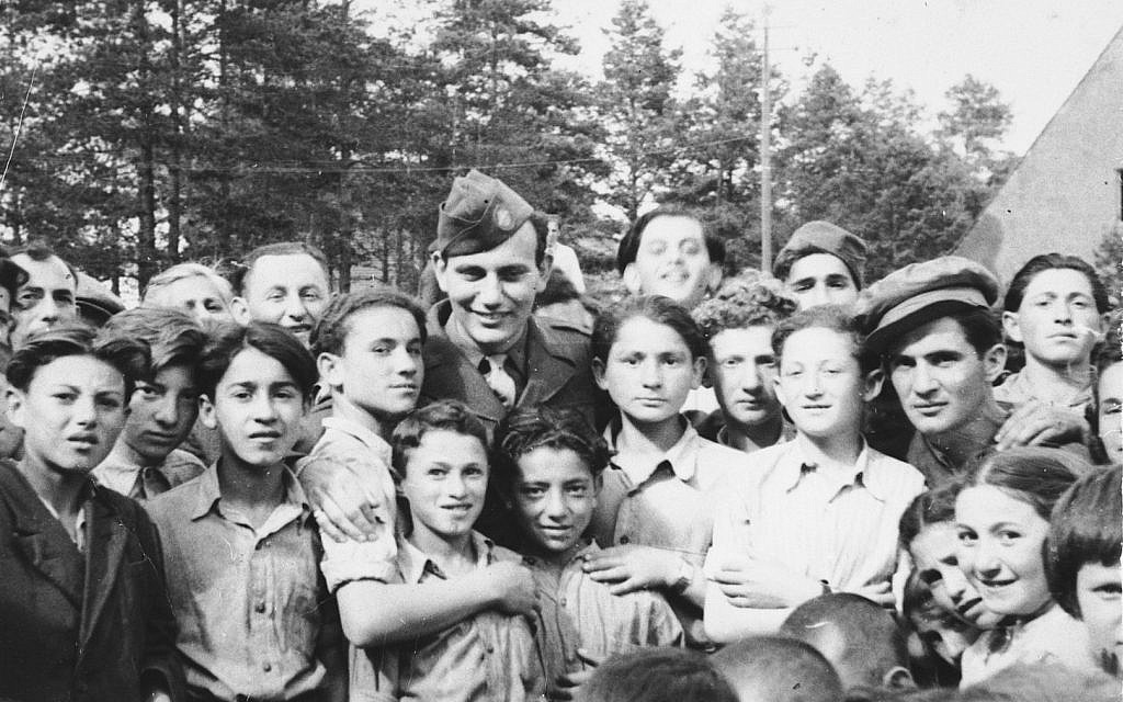 Illustrative: Children at Foehrenwald DP camp gather around a US soldier. (United States Holocaust Memorial Museum, courtesy of Larry Rosenbach)
