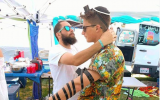 Rabbi Daniel Bortz helps a Coachella music festival attendee put on phylacteries and pray. (Courtesy)