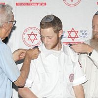 Dvir Shnerb receives shoulder epaulets from his father Rabbi Eitan Shnerb and his grandfather Zvi Wisbert, at the graduation ceremony of the MDA Medics Course. (Madagascar Photography via JTA)