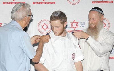 Dvir Shnerb receives shoulder epaulets from his father Rabbi Eitan Shnerb and his grandfather Zvi Wisbert, at the graduation ceremony of the MDA Medics Course. (Madagascar Photography via JTA)