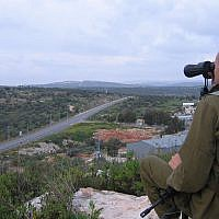 An IDF soldier surveys the area around the village of Azun near the West Bank city of Qalqilya, April 2007. (Roy Sharon/Flash90)