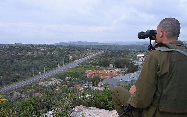 An IDF soldier surveys the area around village of Azun near the West Bank city of Qalqilya, April 2007 (Roy Sharon/Flash90)