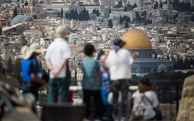 Tourists look at the view of the Dome of the Rock and the Temple Mount from the lookout of the Mount of Olives overlooking the Old City of Jerusalem, on October 11, 2018. (Hadas Parush/Flash90)
