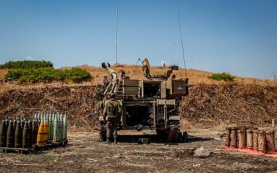 Israeli soldiers stand near artillery units deployed near the Lebanese border outside the northern city of Kiryat Shmona on September 1, 2019. (Basel Awidat/Flash90)