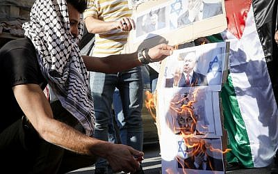 Palestinians burn pictures depicting Israeli Prime Minister Benjamin Netanyahu during a protest against the PM's visit to the West Bank city of Hebron, September 4, 2019 (Wisam Hashlamoun/Flash90)