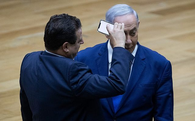 Joint List party leader Ayman Odeh filming Prime Minister Benjamin Netanyahu during a discussion on the cameras bill at the Knesset, in Jerusalem on September 11, 2019 (Yonatan Sindel/Flash90)