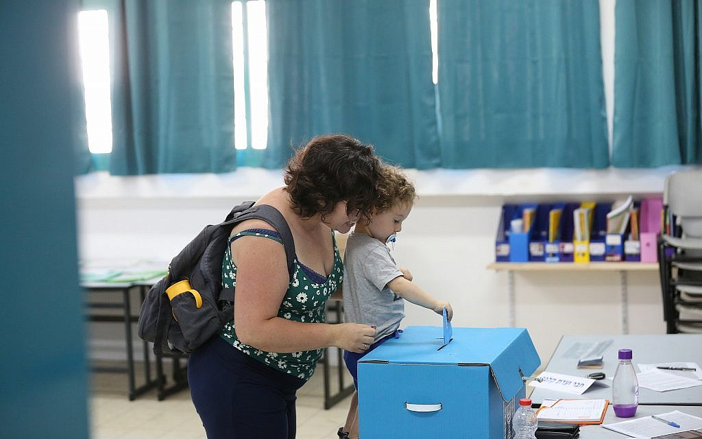 A woman casts her vote with her child at a voting station in Safed, on election day, September 17, 2019. (David Cohen/Flash90)