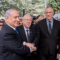 President Reuven Rivlin, Prime Minister Benjamin Netanyahu, and Blue and White leader Benny Gantz, shake hands at the memorial ceremony for the late President Shimon Peres, at the Mount Herzl cemetery in Jerusalem, on September 19, 2019. (Yonatan Sindel/Flash90)