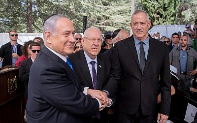 President Reuven Rivlin, Prime Minister Benjamin Netanyahu, and Blue and White leader Benny Gantz shake hands at the memorial ceremony for the late president Shimon Peres, at the Mount Herzl cemetery in Jerusalem, on September 19, 2019. (Yonatan Sindel/Flash90)