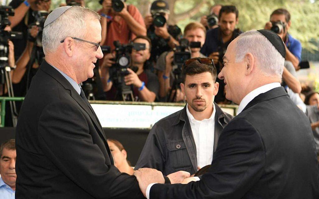 Prime Minister Benjamin Netanyahu (R) and Blue and White party leader Benny Gantz shaking hands during a memorial for former president Shimon Peres in Jerusalem, September 19, 2019. (GPO)