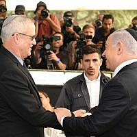 Prime Minister Benjamin Netanyahu (R) and Blue and White party leader Benny Gantz shaking hands during a memorial for former president Shimon Peres in Jerusalem, September 19, 2019. (GPO)