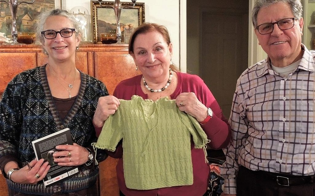 Dr. Kristine Keren (center) holds replica of her green sweater from the Holocaust made from knitting pattern created by Dr. Lea Stern (left). Keren's husband Marion is at right. (Julia Grossman)